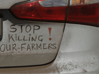 A bumper sign during a blockade of the freeway between Johannesburg and Vereeniging, in Midvaal, South Africa, in protest against the recent murder of farmers, Monday, Oct 30 2017. Traffic was bought to a standstill on highways leading from farming areas to Cape Town, Pretoria and Johannesburg, as white farmers …