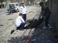 Afghan medical staff recover a dead body at the site of a suicide bombing attack in Kabu on March 21, 2018. A suicide bomber on March 21 killed at least 26 people, many of them teenagers, in front of Kabul University, officials said, as Afghans took to the streets to …