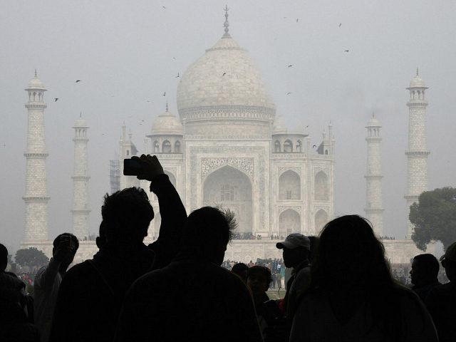 TOPSHOT - Visitors take a photo in front of the Taj Mahal in Agra on January 3, 2018. India is to restrict the number of daily visitors to the Taj Mahal in an effort to preserve the iconic 17th-century monument to love, its biggest tourist draw. Millions of mostly Indian …