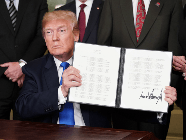 US President Donald Trump signs trade sanctions against China on March 22, 2018, in the Diplomatic Reception Room of the White House in Washington, DC, on March 22, 2018. Trump will impose tariffs on about $50 billion in Chinese goods imports to retaliate against the alleged theft of American intellectual property, White House officials said Thursday. / AFP PHOTO / Mandel NGAN (Photo credit should read MANDEL NGAN/AFP/Getty Images)