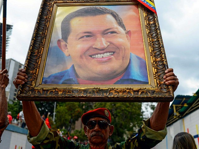 A soldier holds a portrait of late Venezuelan President Hugo Chavez during a rally to commemorate the 26th anniversary of former Chavez's 1992 military coup against the government of Carlos Andres Perez (1989-1993), at the Miraflores presidential palace, in Caracas on February 4, 2018. / AFP PHOTO / FEDERICO PARRA …