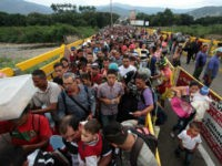 Venezuelan citizens cross the Simon Bolivar international bridge from San Antonio del Tachira in Venezuela to Norte de Santander province of Colombia on February 10, 2018. Oil-rich and once one of the wealthiest countries in Latin America, Venezuela now faces economic collapse and widespread popular protest. / AFP PHOTO / …