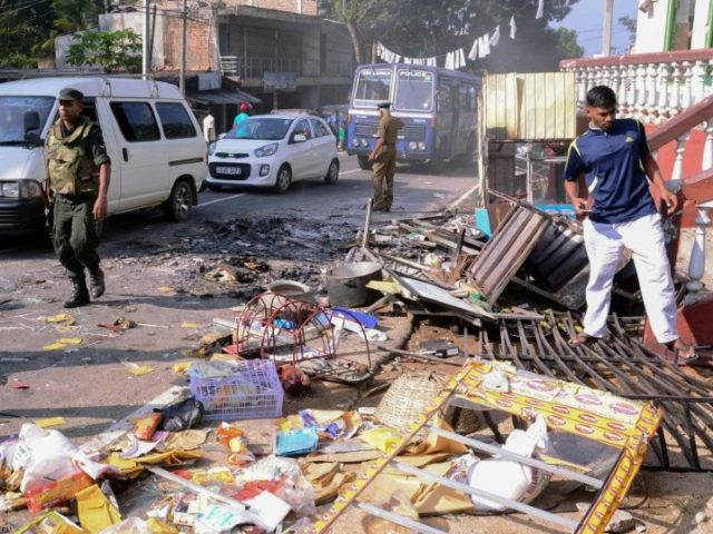 Sri Lankan police commandos patrol next to debris of from a damaged shop in the central district of Kandy on March 6, 2018, after a state of emergency was declared