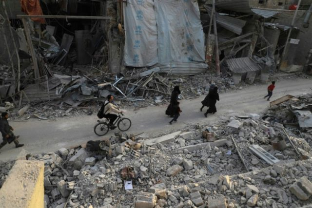 Syrian civilians run from planes following air strikes on the town of Douma as an aid convoy (unseen) entered the rebel enclave of Eastern Ghouta on March 5, 2018