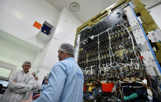 ESA astronaut Tim Peake (L) listens to a technician in the cleanroom explaining details about the Eutelsat Quantum satellite, billed as the first commercial satellite to be fully configurable in orbit, at an Airbus Space and Defence facility in Portsmouth, southern England.