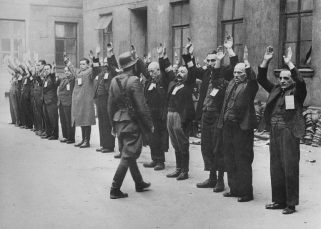 A Nazi SS-man inspects a group of Jewish workers living in the Warsaw Gehotto in April of 1942, an infamous wartime prison in Poland