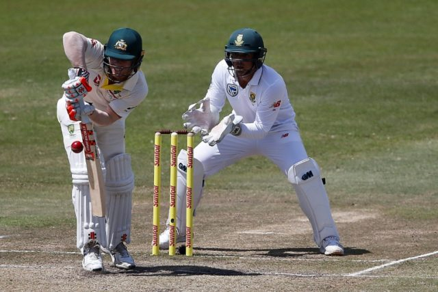 Australian batsman David Warner (L) is watched by South African wicketkeeper Quinton de Kock as he plays a shot on the third day of the first Test cricket match between South Africa and Australia at The Kingsmead Stadium in Durban