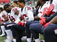 Members of the Houston Texans, including Kevin Johnson and Lamarr Houston, kneel during the national anthem before the game at CenturyLink Field on October 29, 2017 in Seattle, Washington