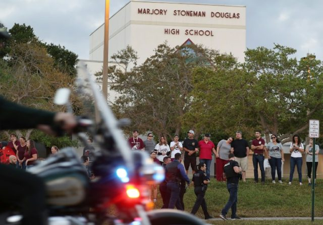People offer support as they stand in front of Marjory Stoneman Douglas High School February 28, 2018, as student arrive to attend classes for the first time since the shooting that killed 17 people on February 14 at the school in Parkland, Florida