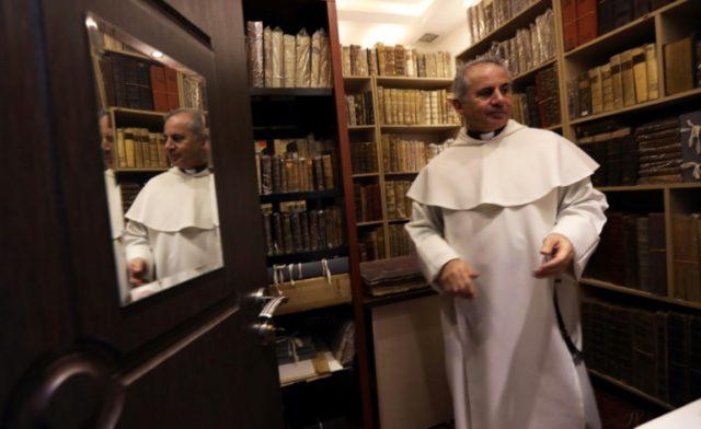 Father Najeeb Michael stands by old Christian books at the Oriental Manuscript Digitisation Centre (CNDO) in Arbil, the capital of Iraq's autonomous northern Kurdish region