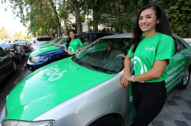 Models stand beside Grab cars in Phnom Penh during the ride hailing-firm's launch in Cambodia in December 2017