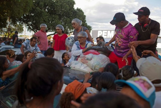 Venezuelan refugees gather to receive clothes distributed by volunteers at the Simon Bolivar square in the Brazilian city of Boa Vista