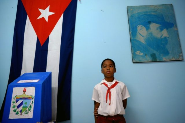 A schoolboy stands at a polling station in Havana during municipal elections in November, 2017, as the communist island moves towards the end of the Castro era
