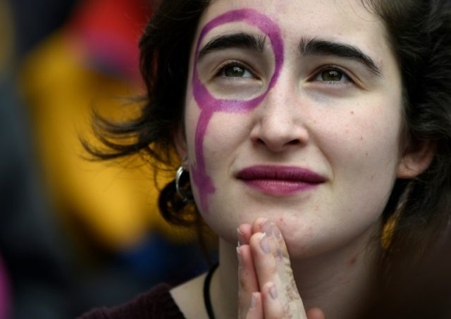 A girl with a Venus symbol on her face attends a protest during a strike to defend women's rights on International Women's Day in Barcelona, on March 8, 2018