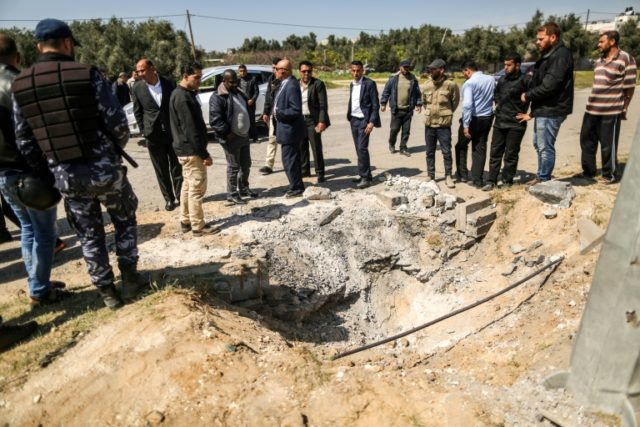 Members of the Hamas security forces inspect the crater left at the site of an explosion that targeted the convoy of the Palestinian prime minister during a visit to the Gaza Strip, on March 13, 2018