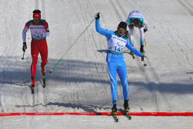 Alexandr Kolyadin (C) of Kazakhstan celebrates his victory in the men's 1.5km sprint classic standing cross-country skiing final