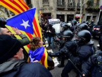 Protesters scuffle with riot police blocking the road leading to the central government offices in Barcelona at a demonstration against the arrest of ex-Catalan president Carles Puigdemont