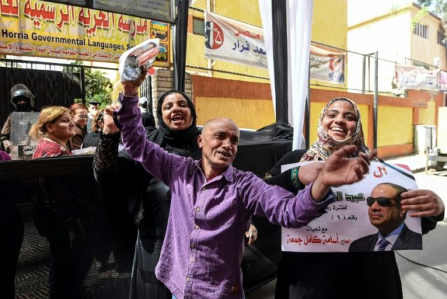 Egyptians dance and celebrate with an electoral poster of incumbent President Abdel Fattah al Sisi outside a polling station in central Cairo