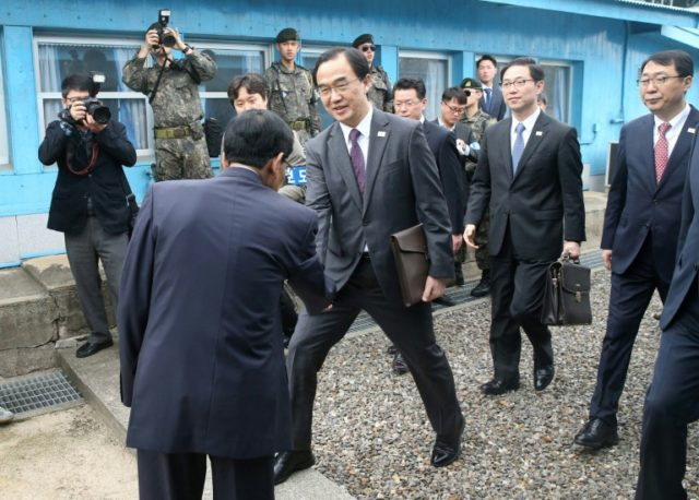 Cho (C) crosses the border line to attend talks held on the northern side of the truce village of Panmunjom