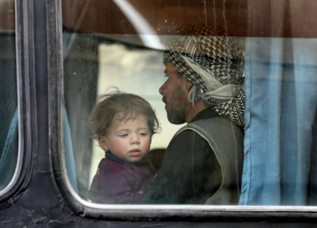 A child looks out of the window of a bus as Syrian civilians and rebels evacuated from the Eastern Ghouta region arrive in Qalaat al-Mandiq, near the central city of Hama, on March 28, 2018, following an evacuation deal
