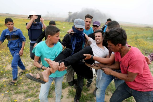 Gazans carry away a protester wounded during a clash with Israeli troops by the border fence near the city of Khan Yunis on March 23, 2018