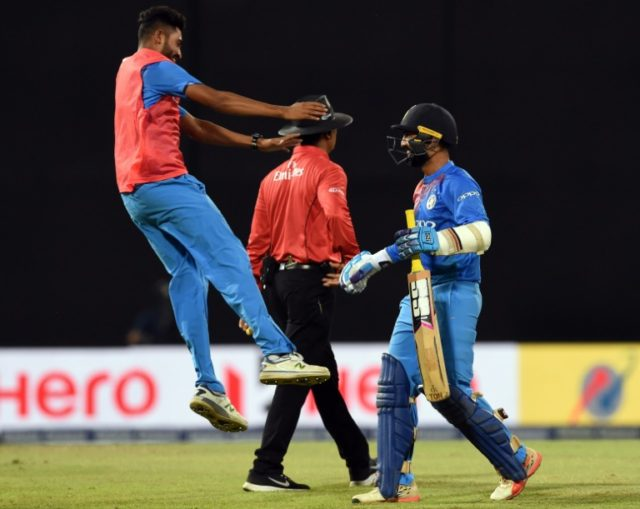 India's Dinesh Karthik (R) scores the winning run to defeat Bangladesh on March 18, a victory which sparked a bizarre fake murder plot by one disappointed punter