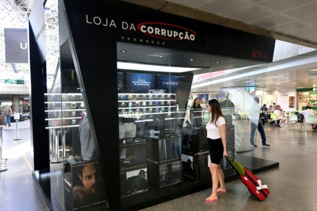 """A passenger stops to take a look at the """"Corruption Shop"""", a kiosk at Brasilia's Airport set up to promote the new Netflix series """"The Mechanism"""" (O Mecanismo), based on Brazil's mammoth """"Car Wash"""" graft scandal, on March 28, 2018"""