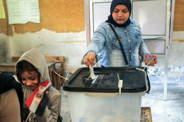 An Egyptian woman casts her ballot at a polling station in the northern port city of Alexandria on the third day of voting in the 2018 presidential elections on March 28, 2018