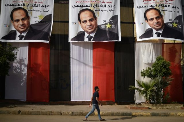 An Egyptian youth walks past a polling station in the capital Cairo's western Giza district on March 25, 2018, ahead of a vote that saw President Abdel Fattah al-Sisi reelected to a second term in office