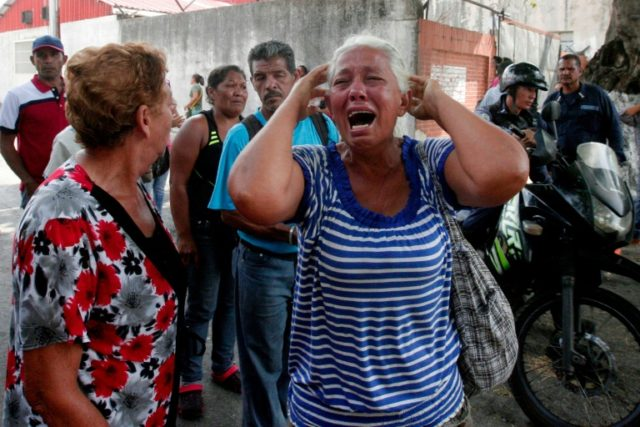 A relative of a prisoner cries in front of a police station in Valencia after a deadly fire that killed 68 people