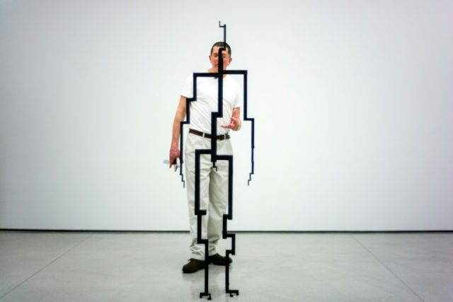Antony Gormley stands next to 'SIGNAL (2017)' at his exhibition 'Rooting the Synapse' in Hong Kong
