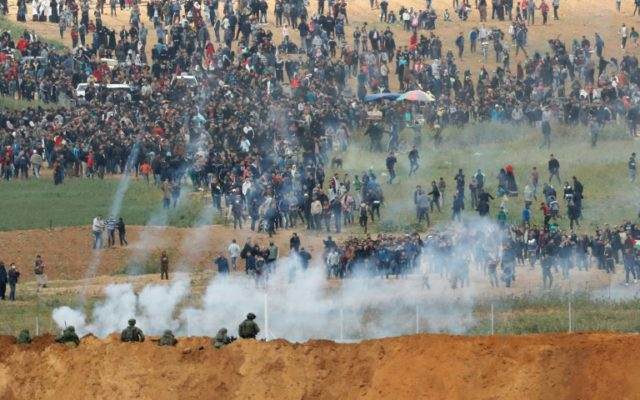 Israeli soldiers fire tear gas as thousands of Gazans march just across the border fence sparking clashes in which four Palestinians were killed and more than 200 wounded