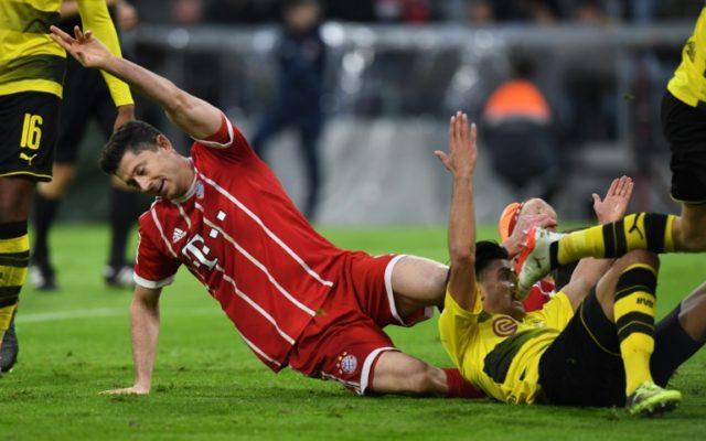 Going nowhere: Bayern Munich striker Robert Lewandowski scores on Saturday against Borussia Dortmund