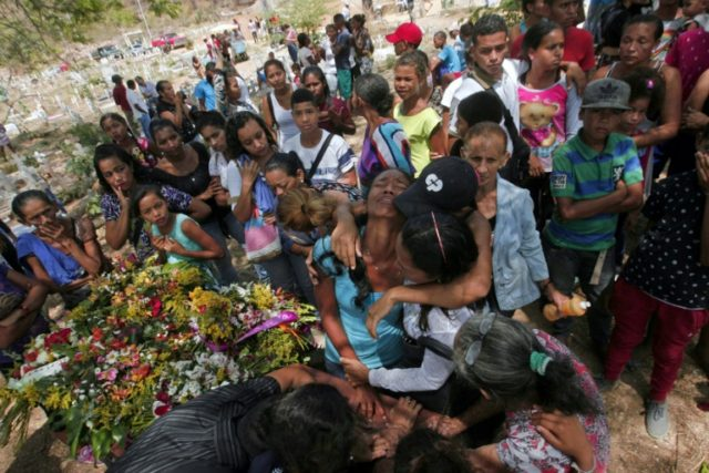 People grieve during a funeral for some of the victims of a deadly prison fire that left 68 dead in Venezuela