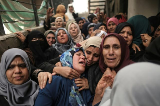 Palestinian relatives of Hamdan Abu Amsha, killed a day earlier by Israeli forces, cry during his funeral in Beit Hanun in the north of the Gaza Strip on March 31, 2018