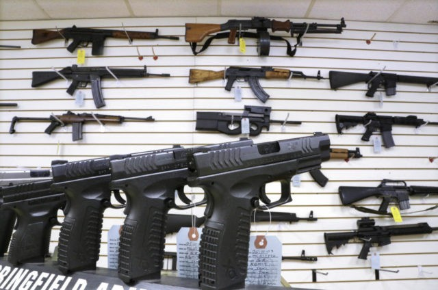 FILE--In this Jan. 16, 2013, file photo, assault weapons and hand guns are seen for sale at Capitol City Arms Supply in Springfield, Ill. Recent mass shootings spurred Congress to try to improve the background check system used during gun purchases, but experts say the system is so fractured that federal legislation being considered in Washington D.C. will do little to help keep weapons out of the hands of dangerous people. (AP Photo/Seth Perlman, file)
