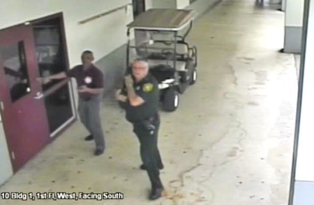 This Feb. 14, 2018 frame from security video provided by the Broward County Sheriff's Office shows deputy Scot Peterson, right, outside Marjory Stoneman Douglas High School in Parkland, Fla. The video released Thursday, March 15, shows Peterson going toward the high school building while a gunman massacred 17 students and …