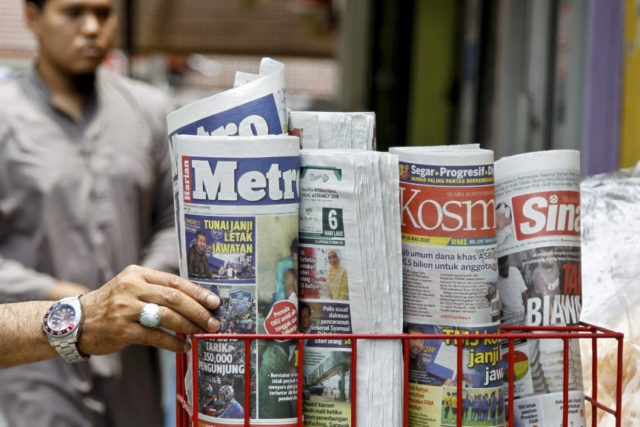 A man takes a copy of newspaper at a grocery shop in Shah Alam, Malaysia, Monday, March 26, 2018. Malaysia's government on Monday proposed new legislation to outlaw fake news with a 10-year jail term for offenders, in a move slammed by critics as a draconian bid to crack down …