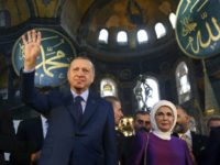Turkey's President Recep Tayyip Erdogan, centre, accompanied by his wife Emine, right, waves to supporters as he walks in the Byzantine-era Hagia Sophia an UNESCO world heritage site and one of Istanbul's main tourist attractions, in the historic Sultanahmet district of Istanbul, Saturday, March 31, 2018. Turkey's president has recited …