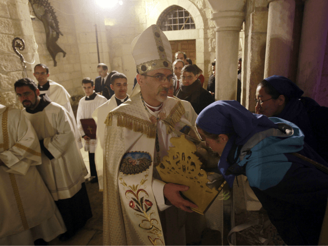 Archbishop Pierbattista Pizzaballa, center, apostolic administrator of the Latin Patriarch of Jerusalem, holds a statue of Baby Jesus in Saint Catherine's Church at the end of the Christmas Midnight Mass and walks in procession to the 'Grotto', where Christians believe the Virgin Mary gave birth to Jesus Christ, in the …