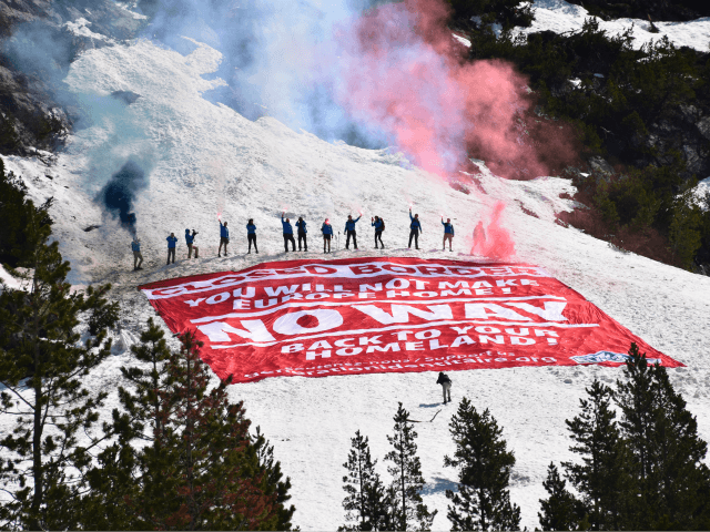 Activists with flares standing above banner