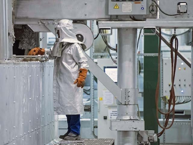 A worker in protective gear checks the production process during the opening of the 200 million euro aluminum recycling and casting center of US company Novelis Inc., headquartered in Atlanta, US, in Nachterstedt, central Germany, Wednesday, Oct. 1, 2014. Located adjacent to the company's existing aluminum rolling mill, the new …