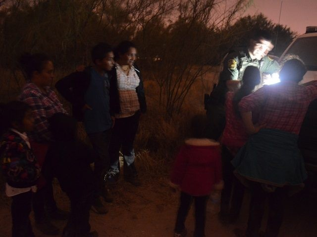 A RGV Sector Border Patrol agent process an illegal immigrant family group at Rincon Bend.