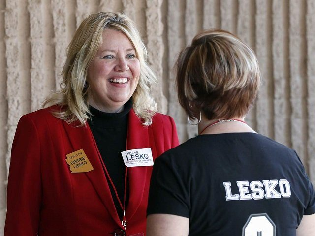 In this Jan. 27, 2018, file photo, Arizona State Rep. and U.S. Representative candidate Debbie Lesko speaks with a constituent during the meeting of the state committee of the Arizona Republican Party in Phoenix. The sprawling suburbs west of Phoenix may put a brake on Democratic optimism following surprising special …