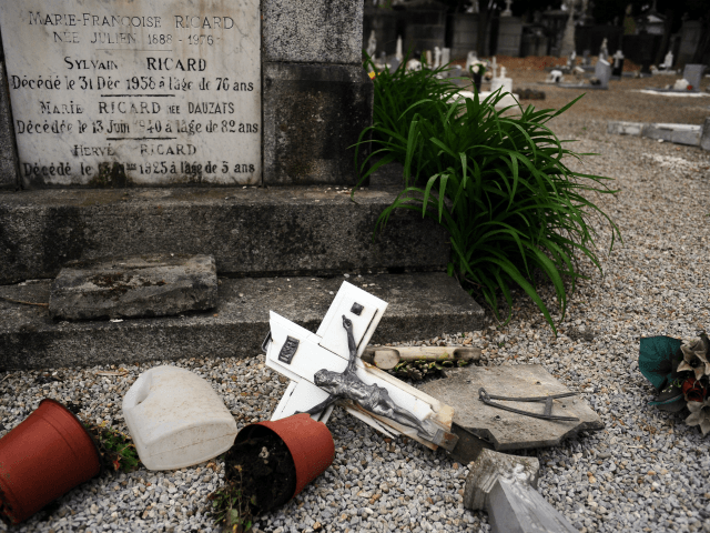 A photo taken on April 15, 2015 shows a crucifix on the floor after tombstones were found vandalized at the Saint-Roch cemetery in Castres, southern France. French President Francois Hollande condemned 'in the strongest terms' the vandalism of 'dozens of Christian tombs' at the Saint-Roch cemetery, qualifying the acts as …