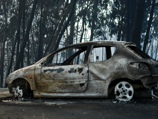 A picture taken on June 18, 2017 shows a burnt car on a road after a wildfire in Pedrogao, in central Portugal. A wildfire in central Portugal killed at least 57 people and injured 59 others, most of them burning to death in their cars, the government said on June …