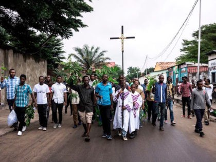 TOPSHOT - A man holds a Catholic cross as he takes part, with a group of Catholic faithfuls, in a demonstration outside the St Francois De Sales Church, during a protest called on by the Catholic Church, to push for the President of the Democratic Republic of the Congo, to …