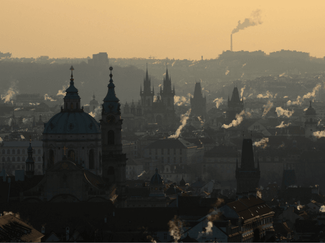 Smoke rises over the rooftops of central Prague with the Saint-Nicolas Church (L) during the sunrise on February 26, 2018, as the temperatures dropped to minus 12 degrees Celsius in the Czech capital. A wintry blast of freezing temperatures sweeps across Europe, with a biting wind from Siberia. The 'Beast …