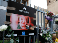 A photograph of Mireille Knoll and flowers are placed on the fence surrounding her building in Paris on March 28, 2018, in memory of the 85-year-old Jewish woman murdered in her home in what police believe was an anti-Semitic attack. The partly burned body of Mireille Knoll, who escaped the …