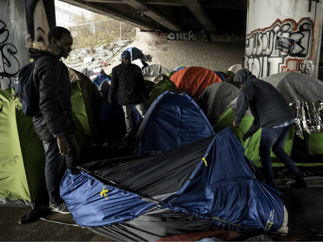 Migrants set up a tent at a makeshift camp set under a bridge along the canal de Saint-Denis in Paris on March 29, 2018. / AFP PHOTO / CHRISTOPHE ARCHAMBAULT (Photo credit should read CHRISTOPHE ARCHAMBAULT/AFP/Getty Images)